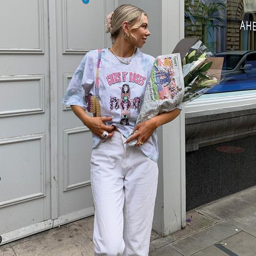 Modella che indossa una T-shirt con stampa e jeans bianchi