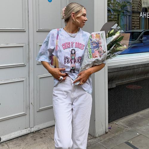 Model in een T-shirt met print en witte jeans