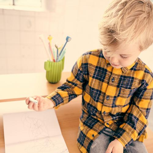 Boy at desk wearing checked shirt