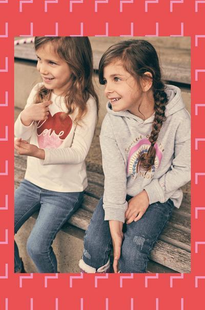 Models wearing rainbow hoodie and heart tee