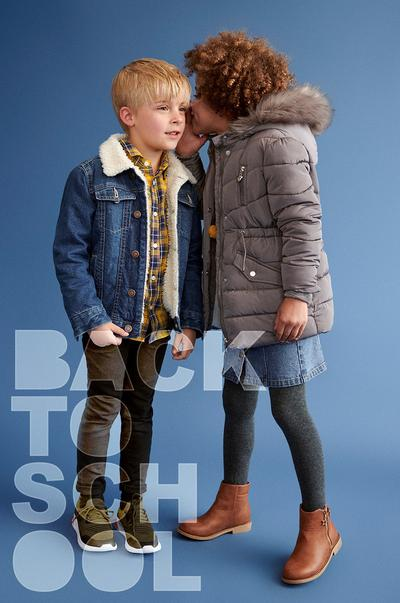 Two kids wearing a denim jacket and coat