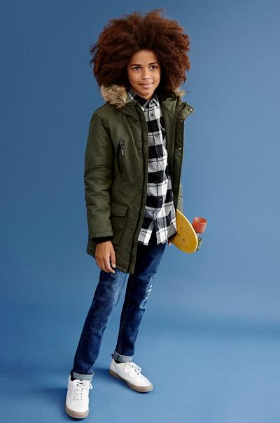 Child wearing an olive jacket, flannel shirt and jeans
