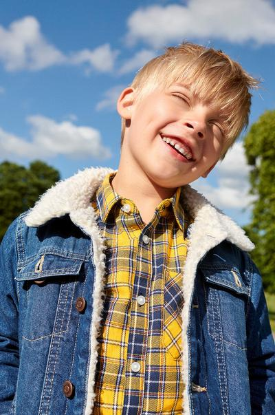Child in a denim jacket and yellow flannel shirt