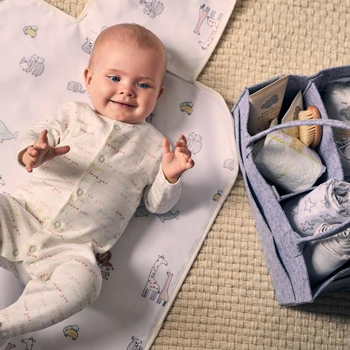 Baby lying on mat with baby accessories