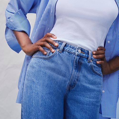 Close up of model wearing blue denim jeans