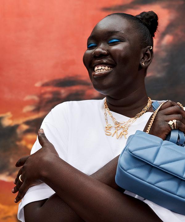 Model wearing white top and blue handbag