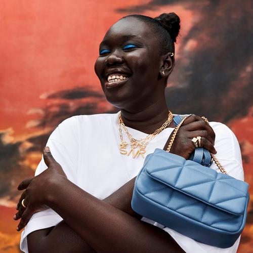Model wearing white top with blue handbag