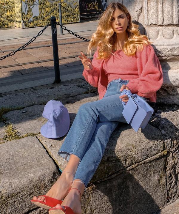 Frau mit rosa Oberteil und blauen Straight-Cut-Jeans