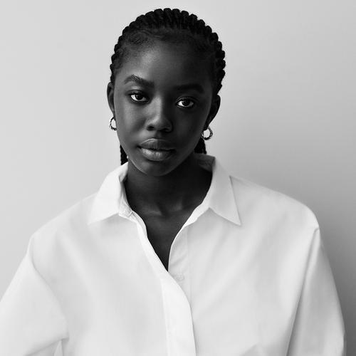 A modelo veste uma camisa branca