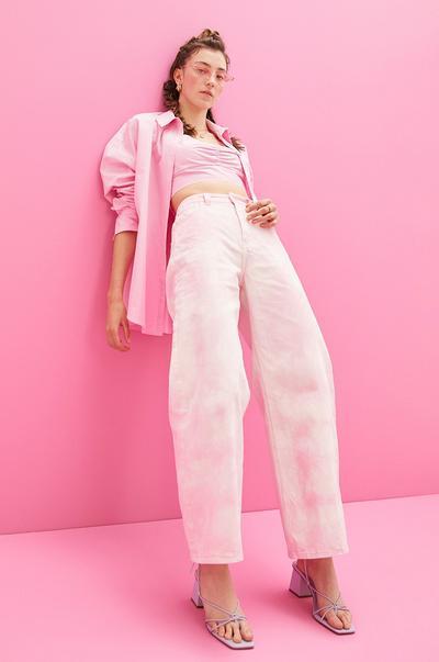 Model mit rosa Hemd, Bralette, Jeans und Sonnenbrille