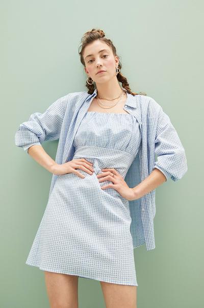 Model in blauem Kleid und Hemd mit Vichy-Karo