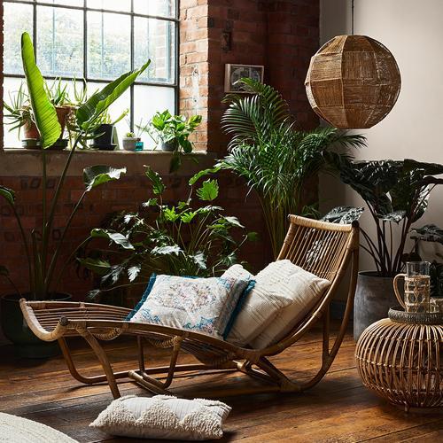 Fotografie domácích interiérů s polštáři, ratanem a umělými rostlinami