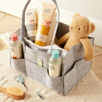 Gray basket with Primark baby products and teddy bea