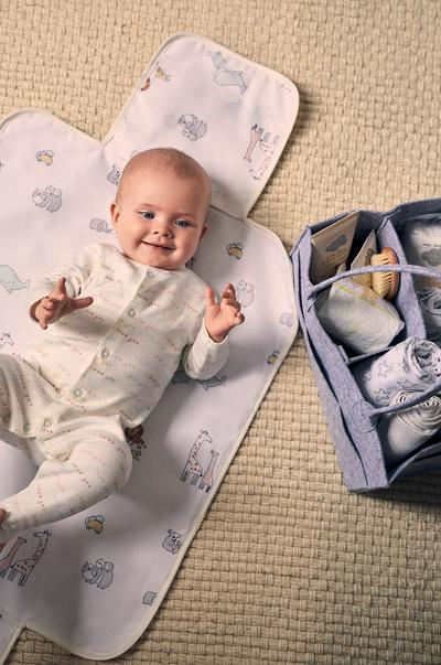 Baby lying on mat with baby accessories, full size