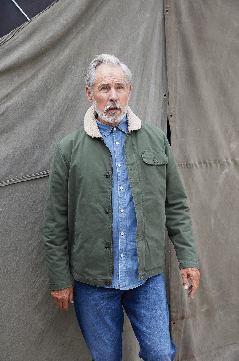 Männliches Model trägt blaue Jeans und grüne Jacke