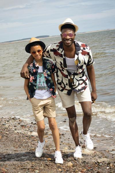 Modelos masculinos con camisas con estampados atrevidos y pantalones cortos en la playa