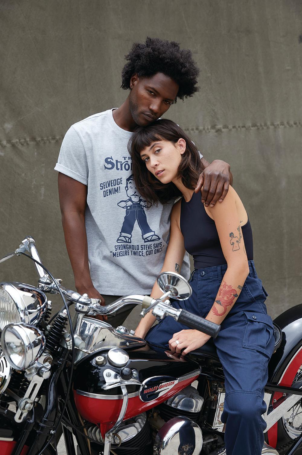 Models tragen Jeans und Oberteile auf/hinter einem Motorrad