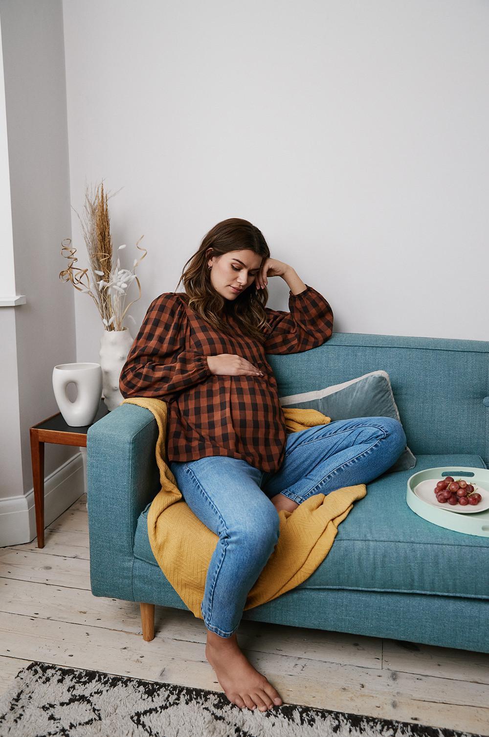 modelo no sofá com top e calças de ganga a olhar para a barriga