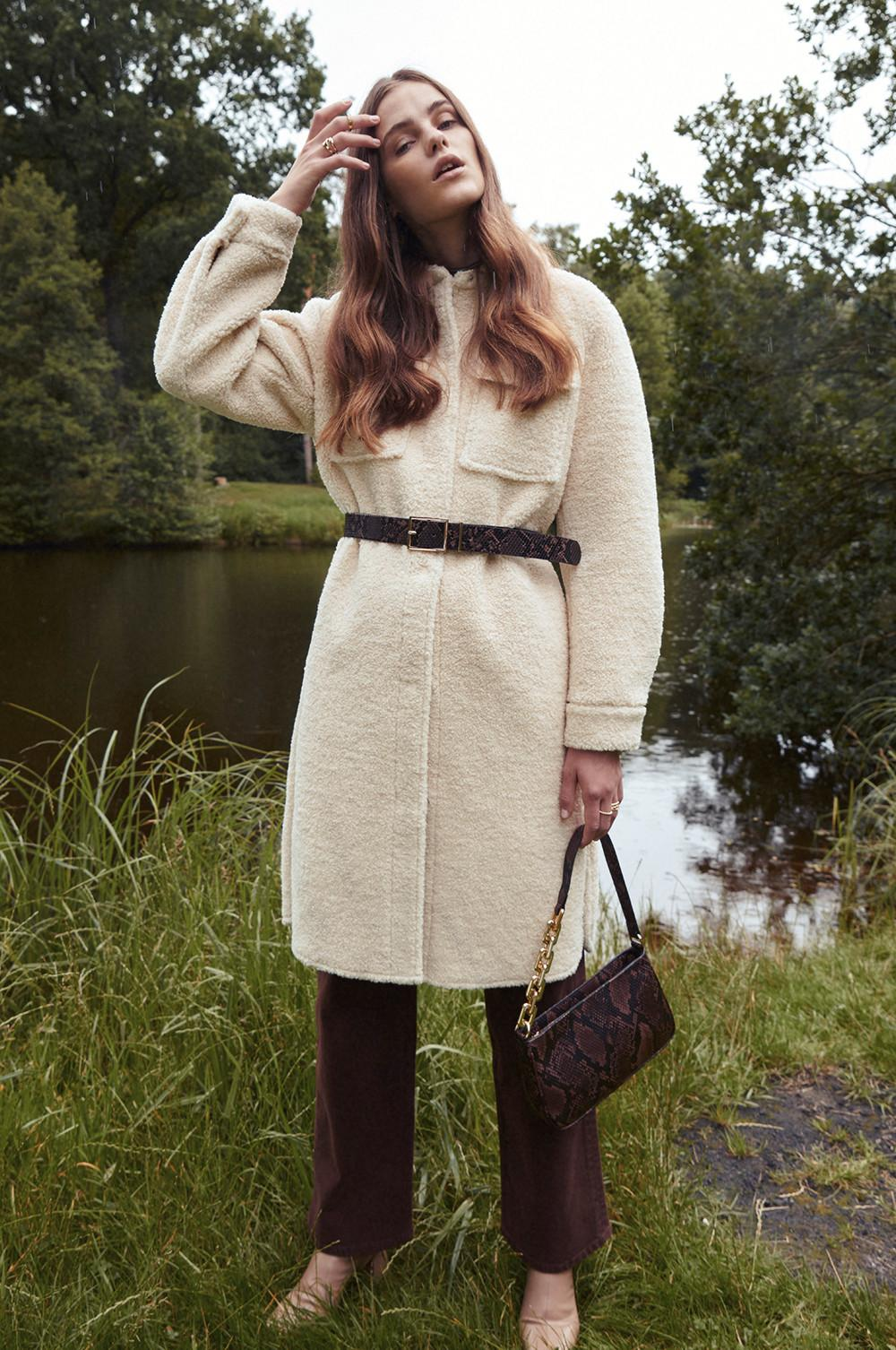 model wears coat with belt over and matching bag