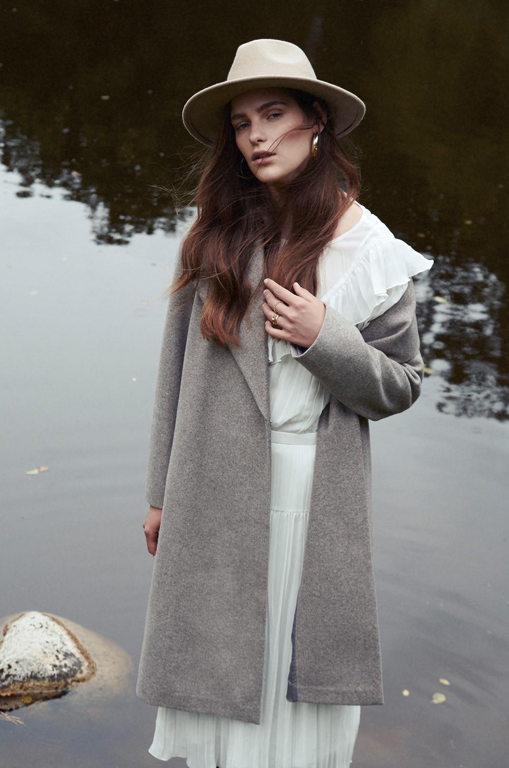 model in grey coat and fedora hat by the water