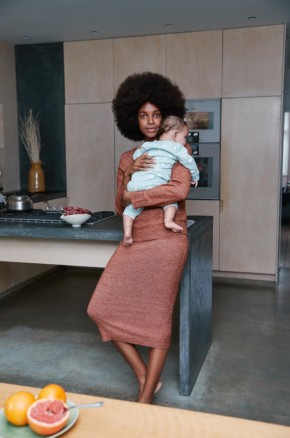 Mãe na cozinha, encostada ao balcão, a segurar no seu bebé. Veste um conjunto coordenado de top e saia laranja-torrado