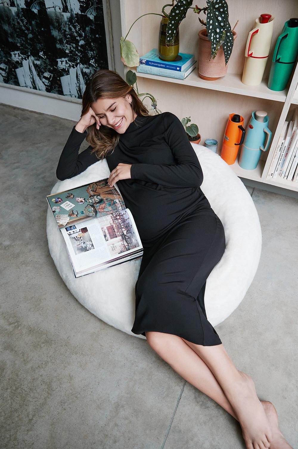 Modelo grávida recostada num pufe, veste um vestido midi preto de manga comprida, enquanto lê uma revista