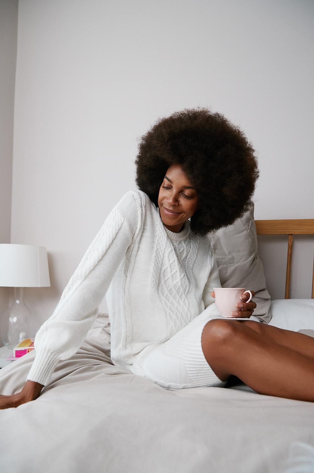 Modelo sentada na cama com um vestido em malha entrançada. A sorrir e a olhar para baixo, ela segura uma chávena de chá equilibrada no joelho