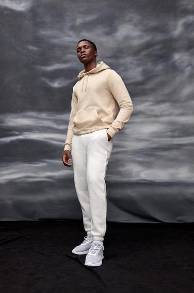 homme en sweat à capuche beige et jean blanc