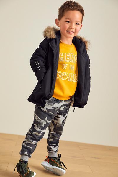 garçon portant une parka et un pantalon motif camouflage
