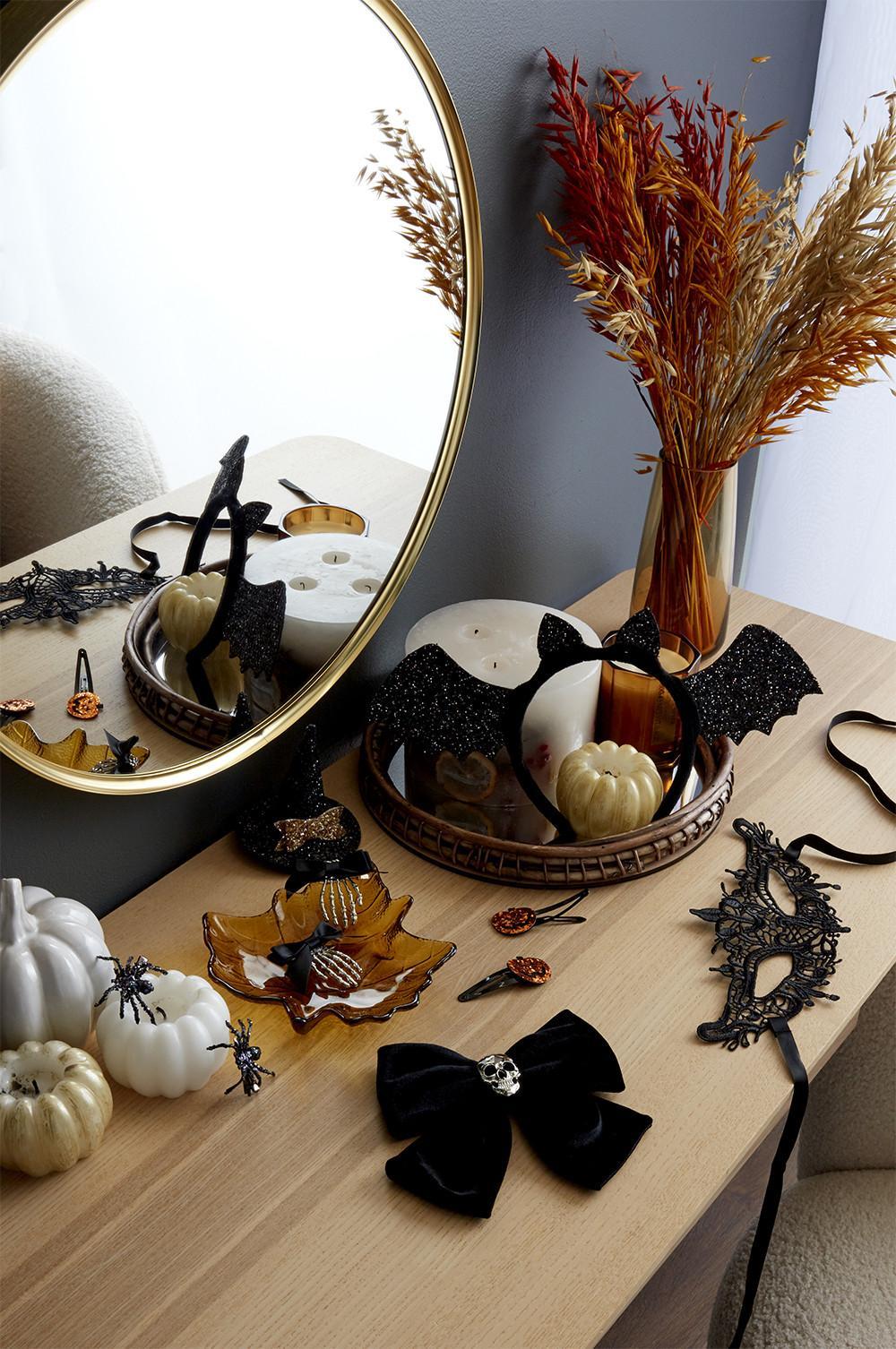image à plat d'accessoires d'halloween, comme des masques, des oreilles de chat, et des serre-têtes chauve-souris.