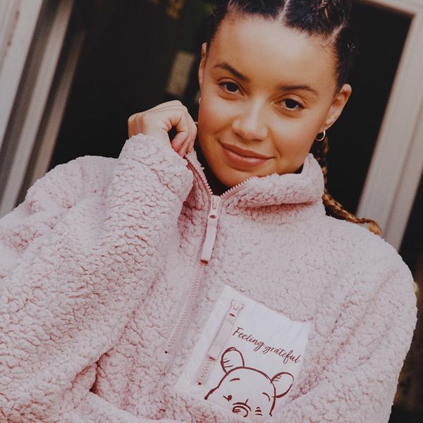 Model wearing pink fluffy fleece with Winnie logo on front