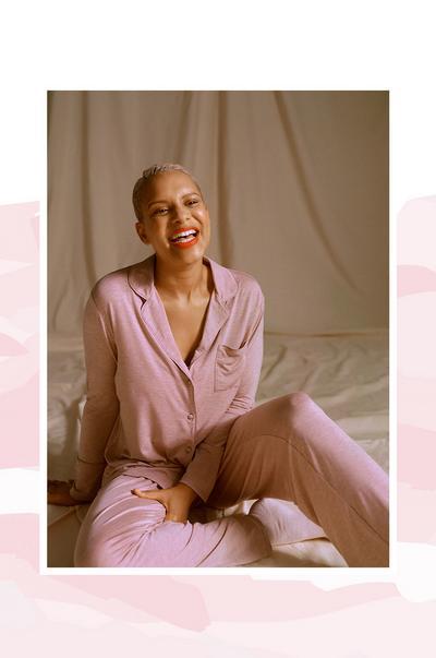 Smějící se modelka sedící na zemi Má na sobě dlouhé, růžové, žerzejové pyžamo se zapínáním na knoflíky a červenou rtěnku