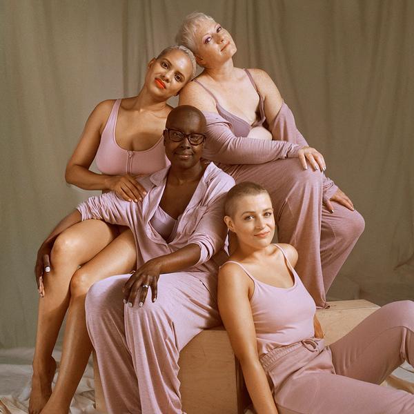 """Models sitzen lachend zusammen und tragen unsere """"Bewusstsein für Brustkrebs""""-Kollektion."""