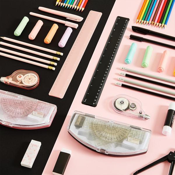 Obrázek rozložených kancelářských potřeb v černé a růžové