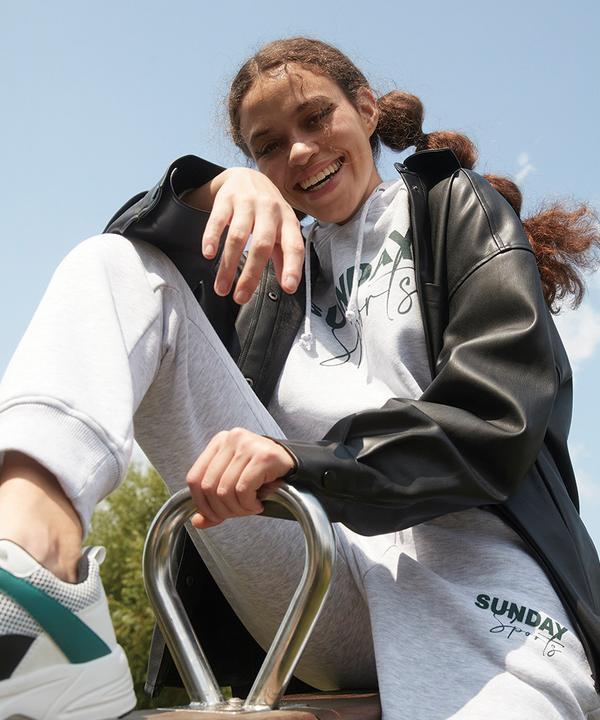 Model in Kapuzenpullover, Jogginghose und schwarzer Hemdjacke