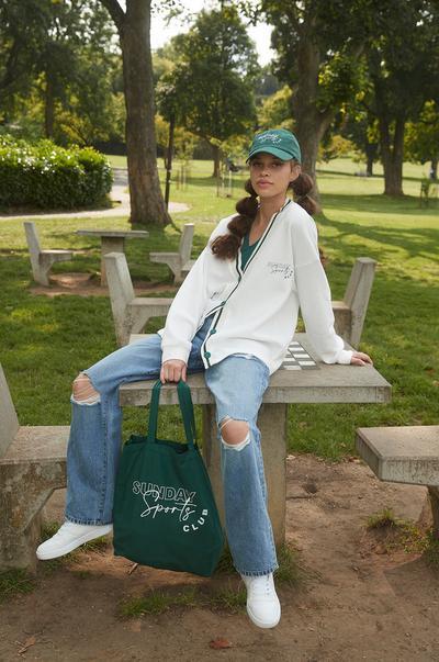 Model in cremefarbenem Cardigan und Jeans mit Rissen