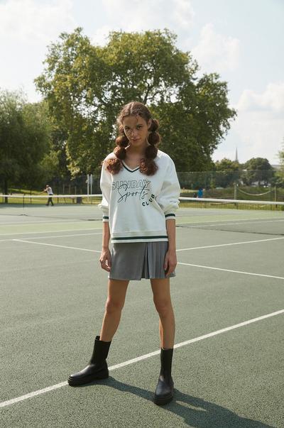 Model in cremefarbenem Pullover und grauem Minirock