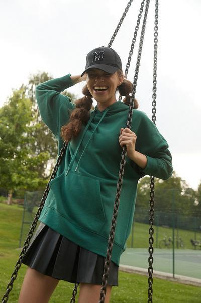 Model in grünem Hoodie und schwarzem Skort