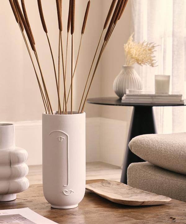 Wohnzimmer mit beruhigendem Ambiente und Vase auf einem Tisch