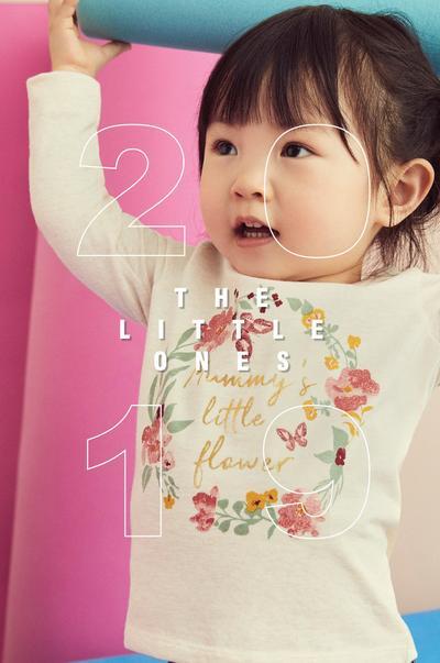 petit enfant portant un t-shirt à fleurs