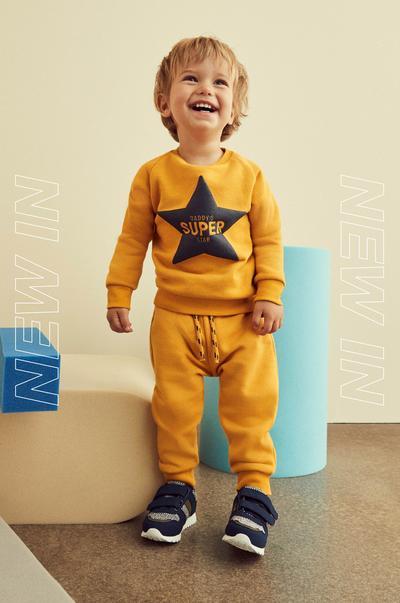 petit enfant portant un ensemble jaune