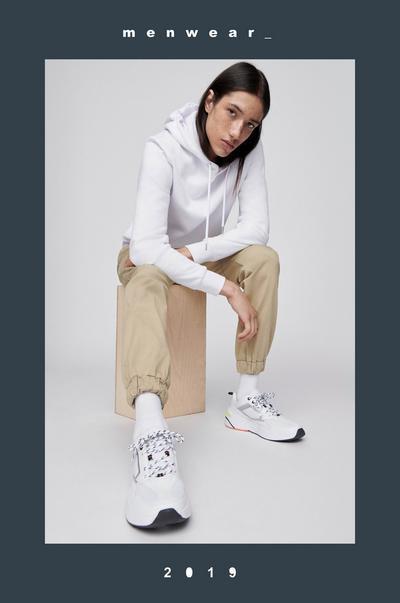 Model in beigefarbener Hose und weißem Kapuzenpullover