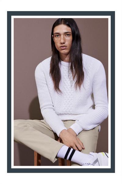 Model in weißem Top und beigefarbener Hose