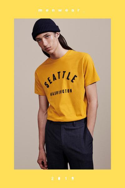 Model in gelbem T-Shirt mit aufgedrucktem Ortsnamen