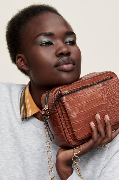 Femmes portant un sac marron effet croco