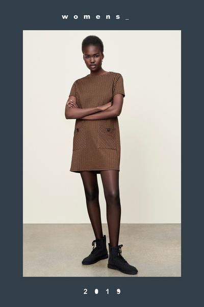 Model in Kleid mit Hahnentrittmuster