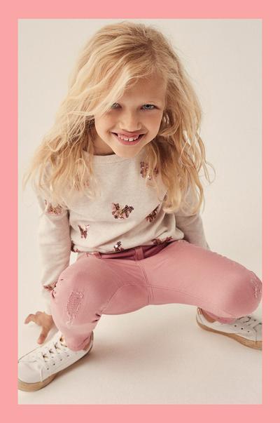 rapariga com calças de ganga cor-de-rosa