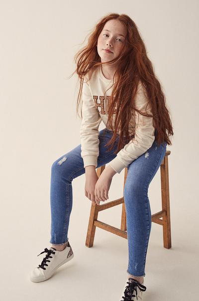 rapariga com calças de ganga e camisola