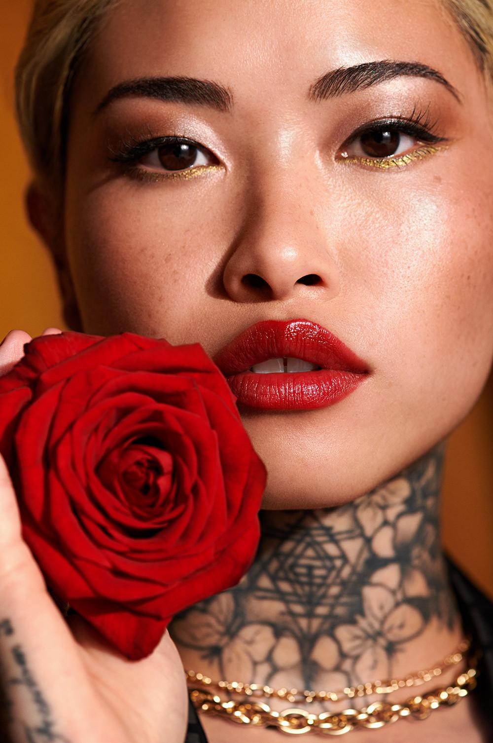 Mannequin tenant une rose rouge, maquillée avec un rouge à lèvres rouge et un eye-liner noir et doré, et portant une chaîne dorée autour du cou.