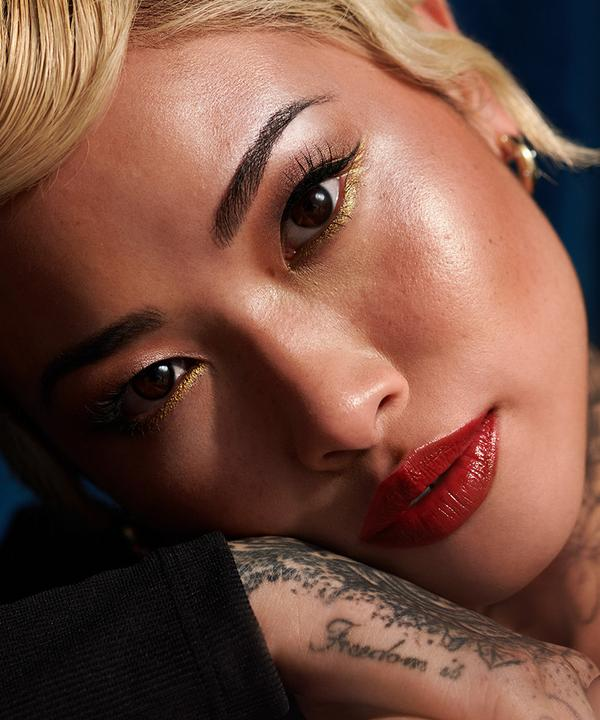 Mannequin tatouée portant un maquillage Eastern Bloom avec rouge à lèvres rouge